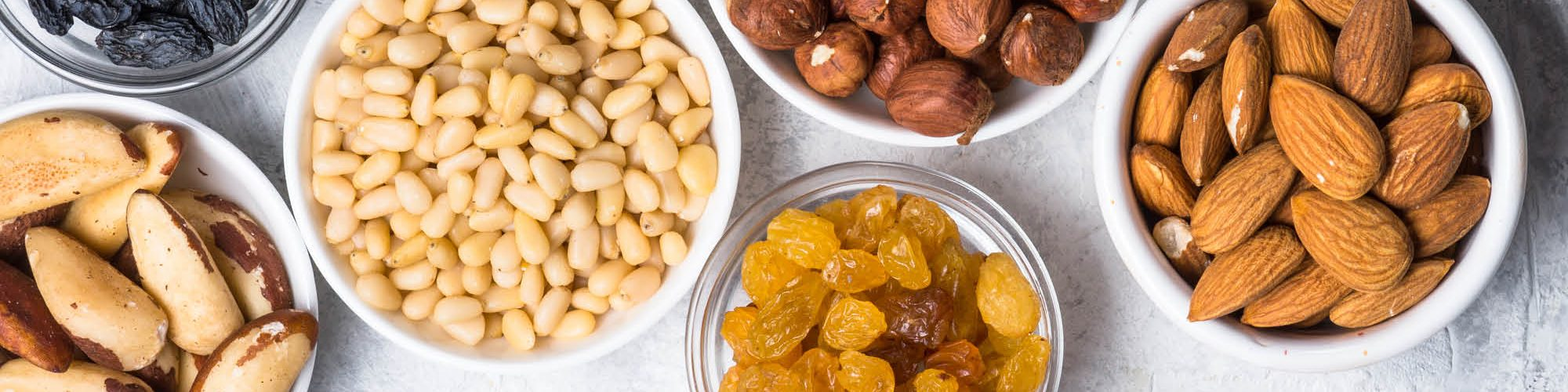 Lots of small bowls of dried fruits and nuts on a marble counter